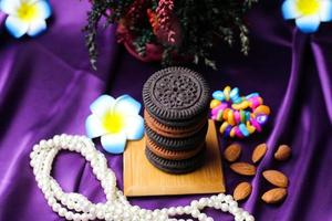 Delicious cookies and nuts with flowers photo