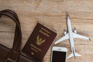 Leather bag and Small plane model on wooden board background photo