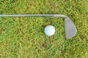 Palos de golf y pelota de golf sobre fondo de hierba verde foto