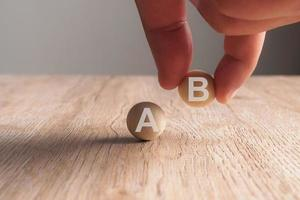 Hand putting on A-B word written in wooden ball photo