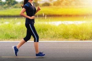 hermosa niña corriendo en la carretera, entrenamiento de mujer fitness saludable foto