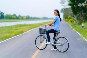 niña con bicicleta, mujer en bicicleta en la carretera en un parque foto