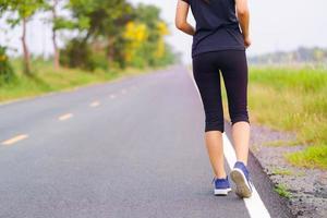 Pies de mujer corriendo en la carretera, entrenamiento de mujer de fitness saludable foto