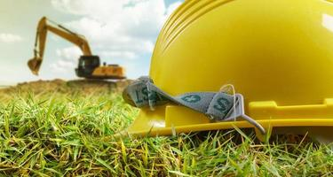 Yellow helmet and excavator working at construction site photo