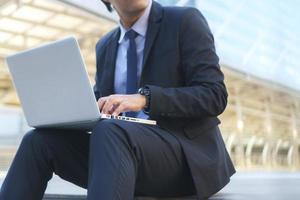 Businessman sitting on the footsteps with laptop photo