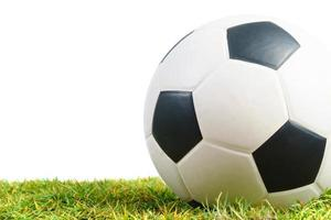 Soccer ball on green grass isolated on white background photo