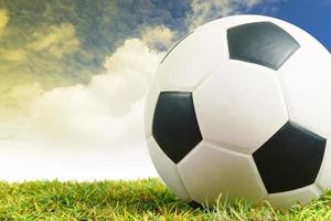 Soccer ball on green grass background photo