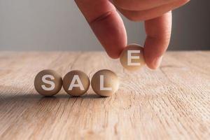 Mano poniendo en venta palabra escrita en bola de madera foto