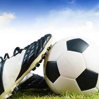 Soccer ball and shoes on grass photo