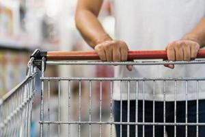Close-up of Man pushing shopping cart in a supermarket photo