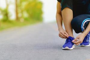 Girl runner trying running shoes getting ready for jogging photo