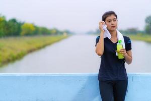 Retrato de una hermosa niña en ropa deportiva con una botella de agua foto
