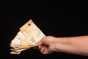 Billetes de dinero en mano sobre fondo negro foto