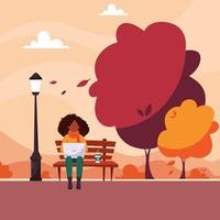 Black woman freelancer with laptop sitting on bench in autumn park vector
