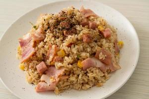 Fried rice with bacon, ham, and black peppers on white plate photo