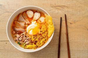 fideos de huevo con carne de cerdo y albóndigas en sopa picante o fideos tom yum al estilo asiático foto
