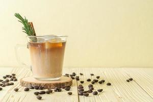 Verter la leche en un vaso de café negro con cubitos de hielo, canela y romero sobre fondo de madera foto