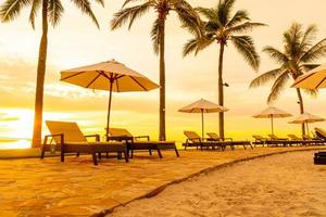 Umbrella and chair around swimming pool in hotel resort with sunrise in morning photo