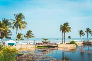 Puente con palmera de coco y playa de mar y fondo de cielo azul foto