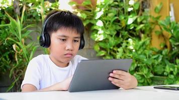 les garçons portent des écouteurs sans fil et utilisent une tablette video