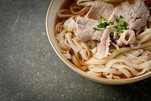Homemade udon ramen noodles with pork in soy or shoyu soup photo