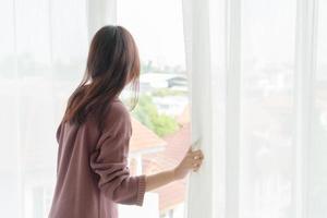 hermosa mujer asiática abre la cortina por la mañana foto