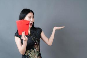 Beautiful Asian woman wear Chinese traditional dress with red envelope or red packet on grey background photo