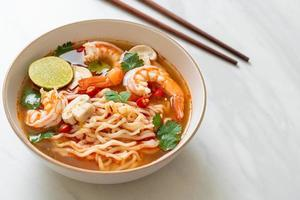 Instant noodles ramen in spicy soup with shrimp Tom Yum Kung - Asian food style photo