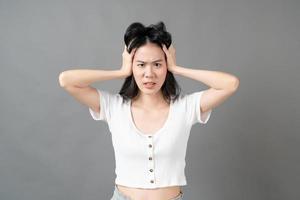 Joven mujer asiática con cara seria y tensa en camisa blanca sobre fondo gris foto
