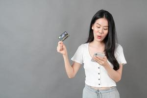 Young Asian woman using phone with hand holding credit card - Online shopping concept photo