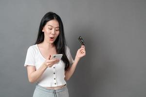 Mujer asiática joven que usa el teléfono con la mano que sostiene la tarjeta de crédito - concepto de compras en línea foto