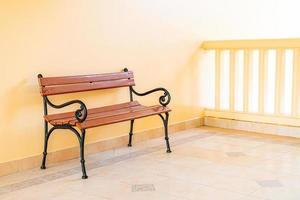 Empty bench with yellow wall photo