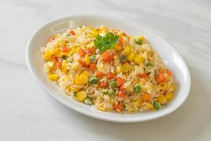 Homemade fried rice with mixed vegetables of carrot, green bean peas, corn, and egg photo