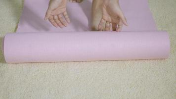 Asian young woman rolling fitness yoga pink mat before sports practice for exercise, female working out at home in the living room. lifestyle sport healthy concept, slow motion from 60fps video