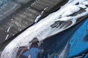 Primer plano de coche gris con espuma de lavado foto