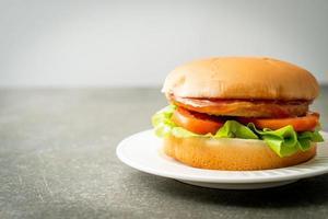 Hamburguesa de pollo con salsa en la placa blanca. foto