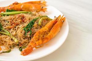 Fideos de arroz salteados y mimosa de agua con gambas de río foto