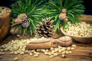 Cedar cones and nuts on olive wood photo
