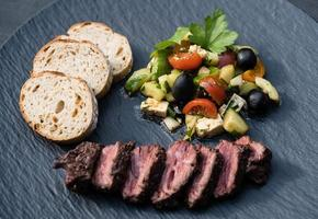 grilled Kidney cones beef with bread and salad photo