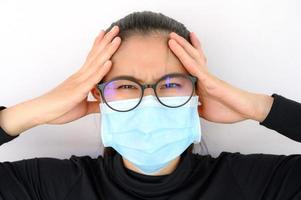 Young Asian woman having headache while wearing medical mask for protect bad air pollution photo