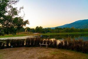 Wood bench with beautiful lake at Chiang Mai with forested mountain and twilight sky in Thailand . photo