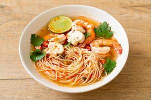Noodles with spicy soup and shrimps in white bowl - Tom Yum Kung  - Asian food style photo