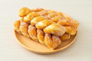 Sugar doughnut in spiral shape on wooden plate photo