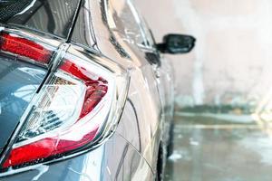 Lámpara de faro de coche de primer plano con espuma de lavado de coches foto