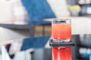 Glass of punch juice on table photo