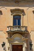 Italy, Lecce, city with Baroque architecture and churches and archaeological remains.  Ancient baroque window photo
