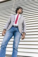 hombre de negocios negro con traje caminando en el fondo urbano. foto