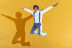 Hombre negro con cabello afro saltando sobre un fondo urbano amarillo foto