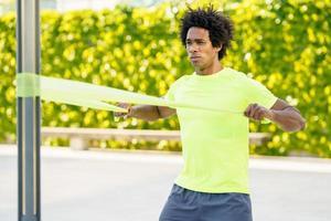 Hombre negro trabajando con banda elástica en el exterior foto
