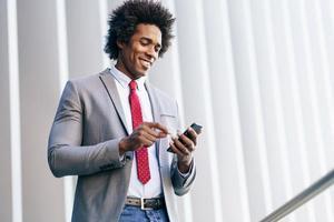 Black Businessman using a smartphone near an office building photo